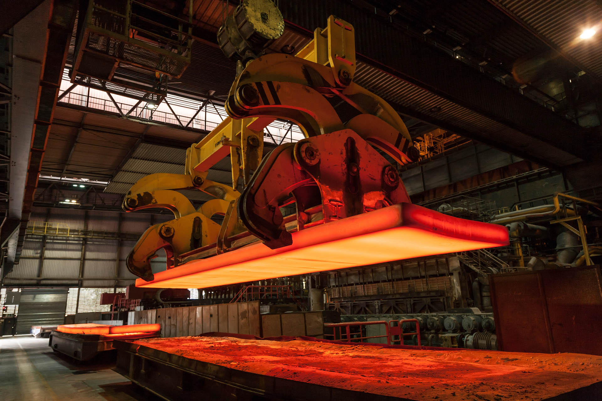 Metal crane moving a hot mass of steel with power